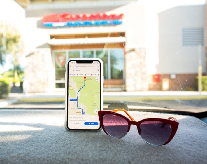 iPhone maps and sunglasses on a car dashboard