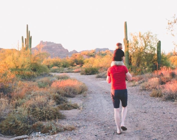 Kid on dad's shoulders on a desert road