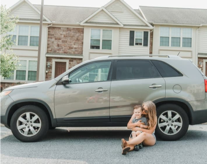 Mom and son in front of car