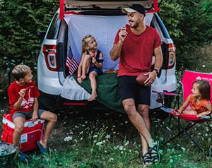 Family tailgating in the back of an SUV
