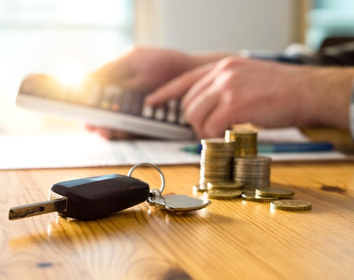 Car keys and a stack of coins on a table while a man types on a calculator