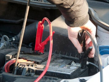 Guy in brown coat jumpstarting a drained car battery