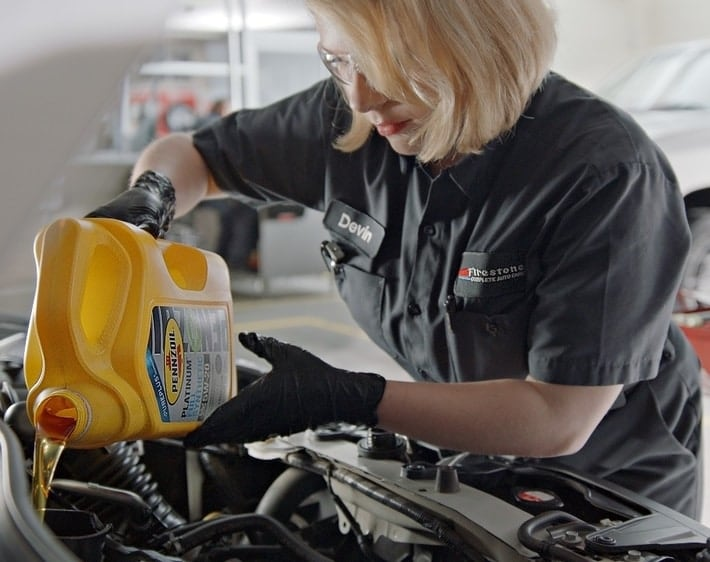 Firestone mechanic pouring Pennzoil motor oil into an engine