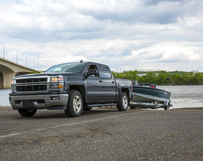 Truck pulling a boat from a lake