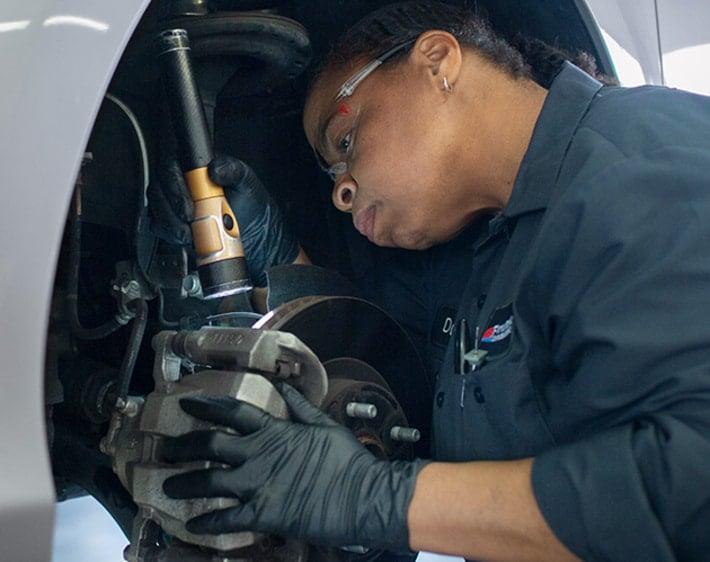 Firestone technician inspecting brake calipers