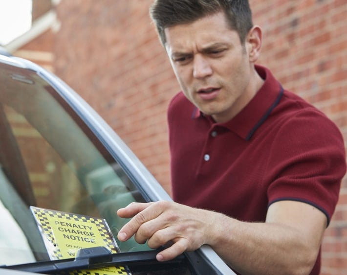 Man looking confused by parking ticket