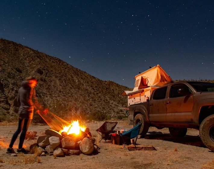 man camping next to truck