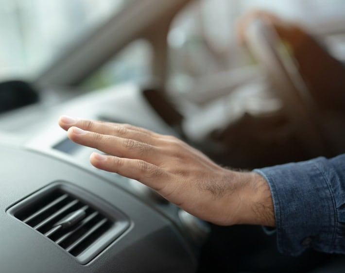 Person feeling air out of car vent