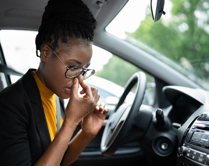 woman sitting in car holding her nose