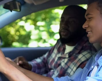 Dad looking at smiling son gripping steering wheel of vehicle