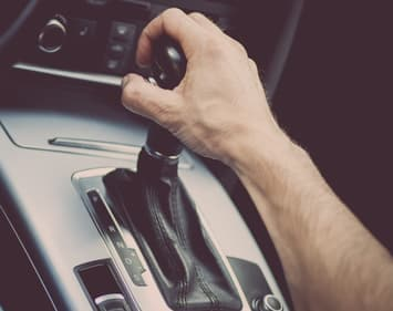 Male hand gripping gear shifter of vehicle