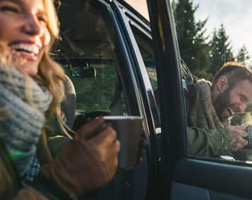 smiling couple sitting in vehicle holding hot mugs with doors open in winter