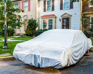 Car covered in sheet sitting in driveway