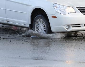 Car Passenger Tire Running Over Pothole