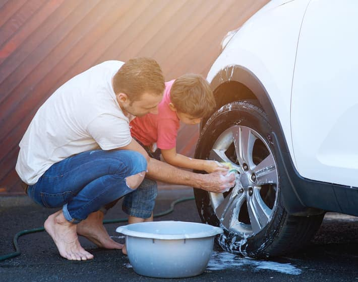 Father and son cleaning car tire together.