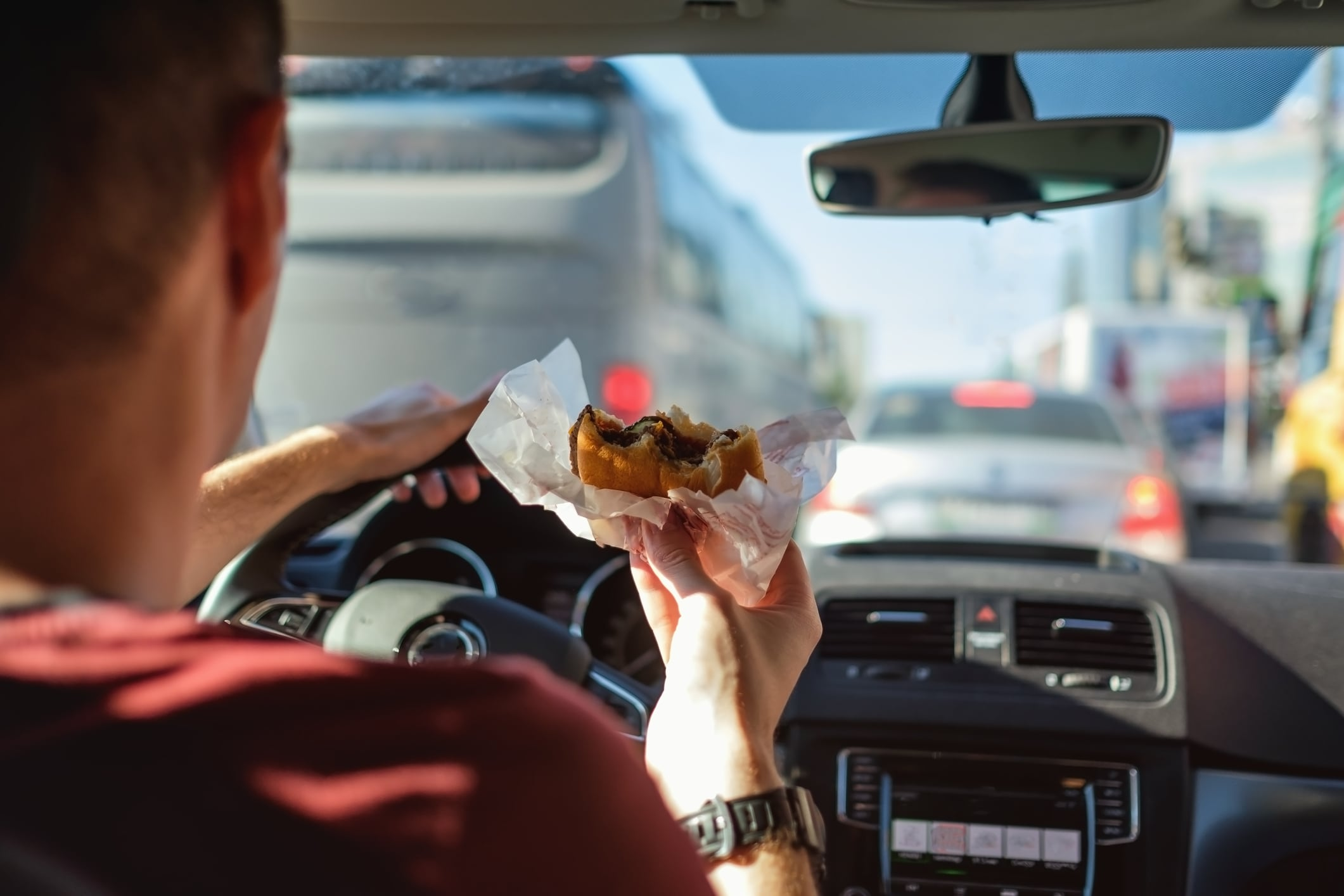 Image of a man eating while driving
