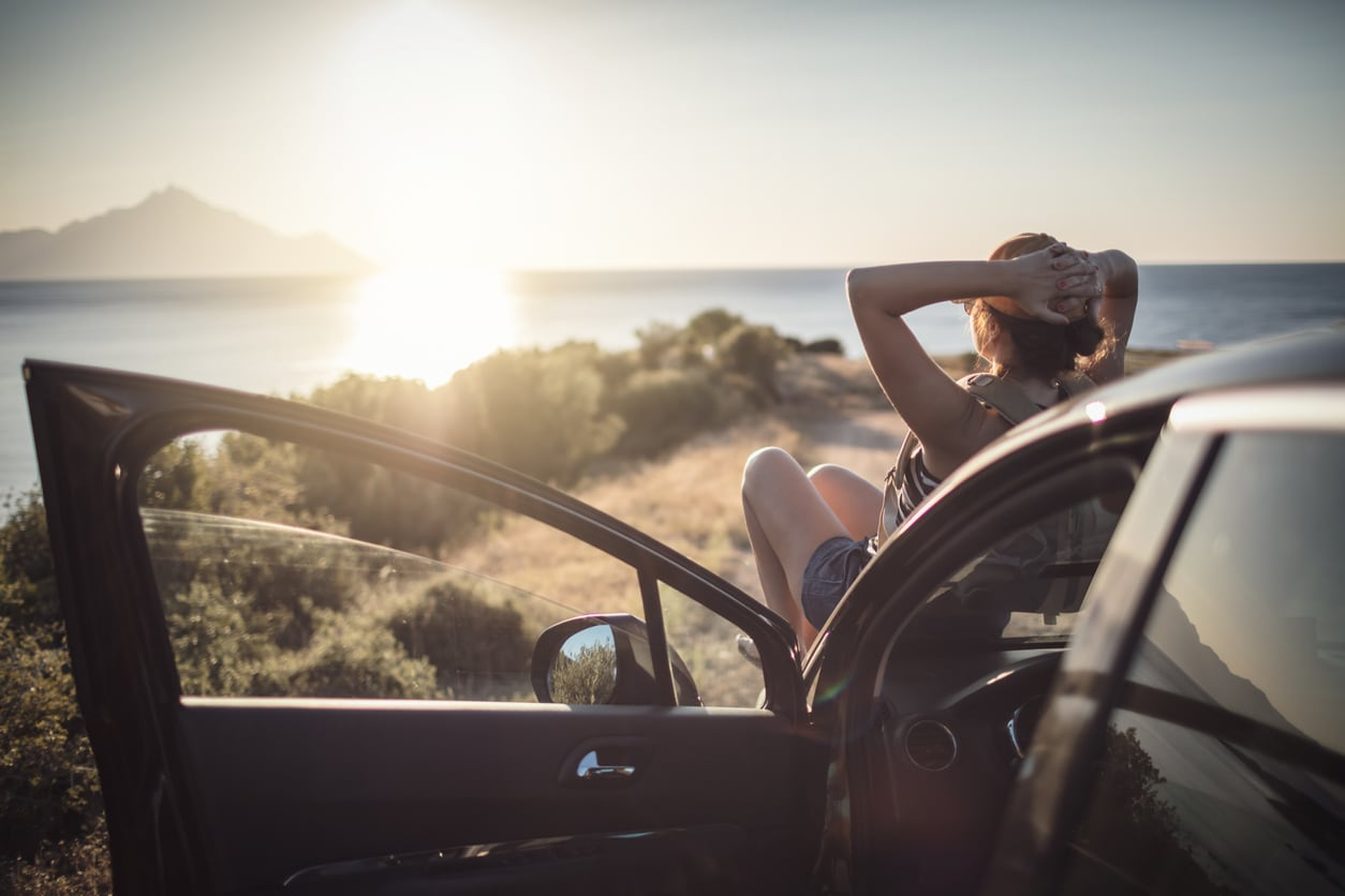 image of woman sitting on her car watching a sunset